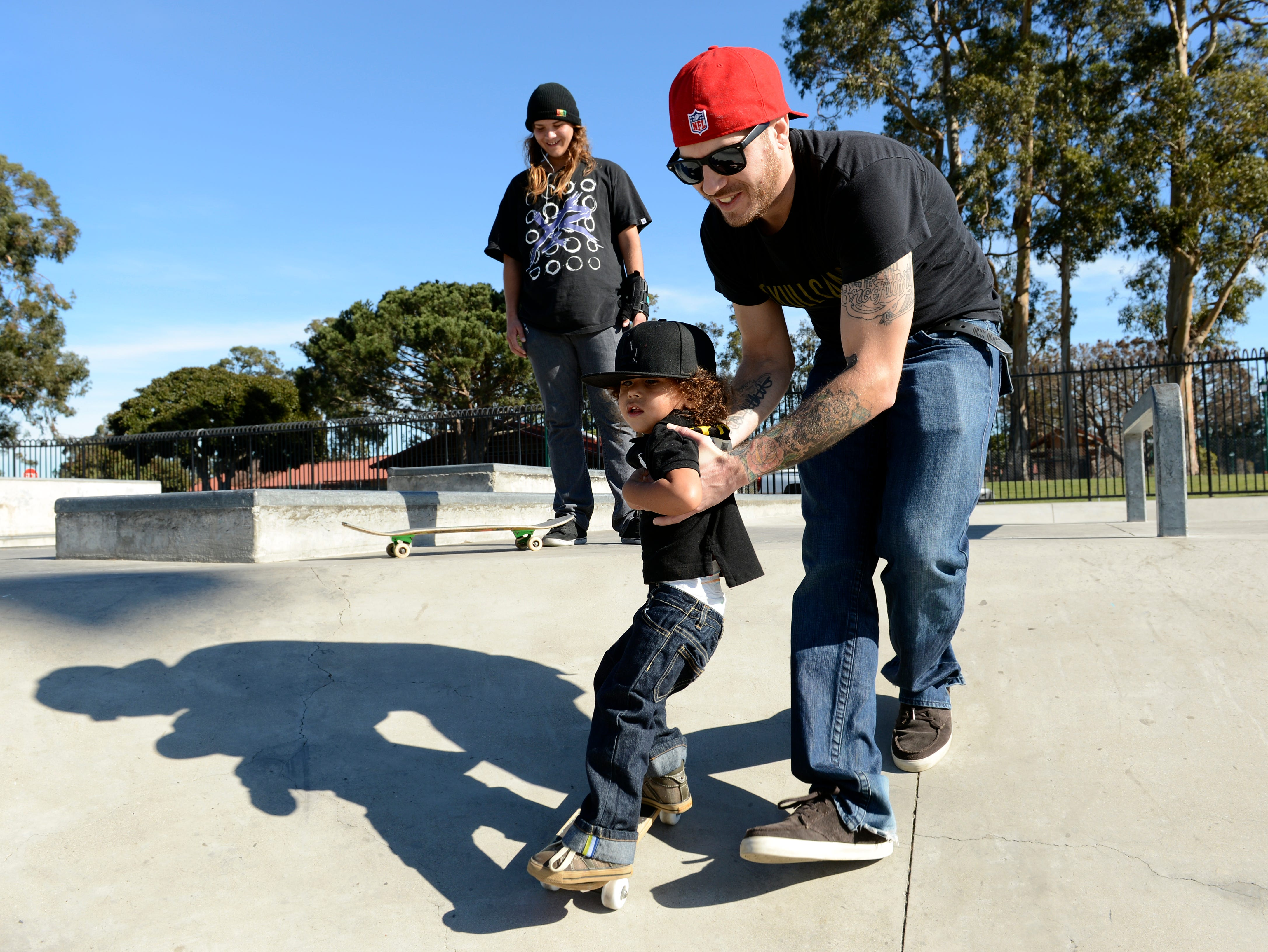 A toddler gets help on the skateboard from his father in this 2013 photo. The Oxnard skatepark is named after former Councilman Bedford Pinkard.