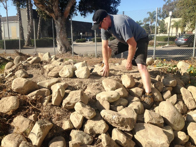 Doug Bell, of Canada, begins the early stages of building a cairn in a lot behind the Museum of Ventura County in Ventura. The display is part of the annual Stonework Symposium taking place through Sunday at the museum.