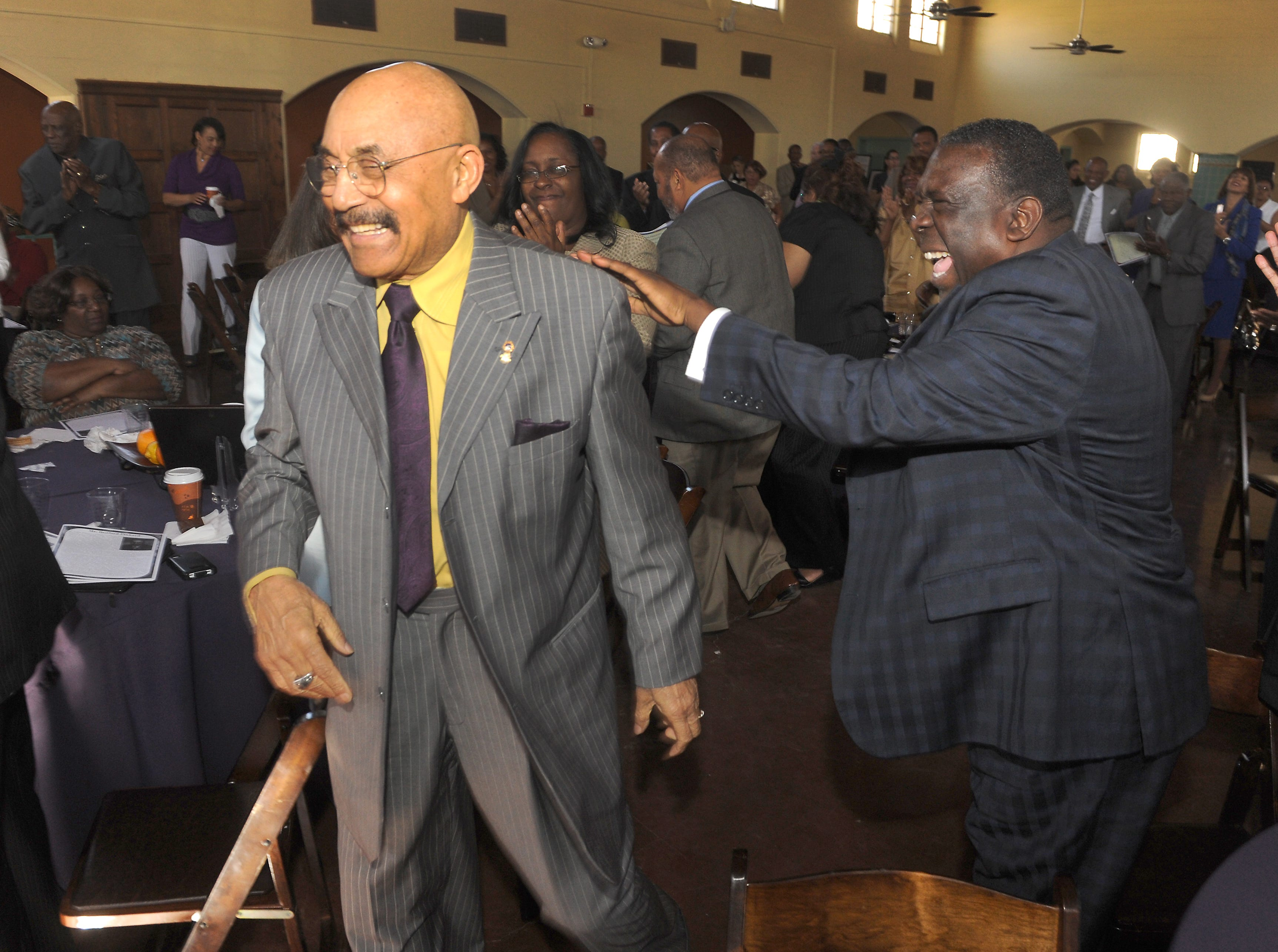 Bishop Broderick Alan Huggins, right, jokes with Bedford Pinkard as he goes up to accept his award in the field of politics at the a CSU Channel Islands African-American Achievement luncheon in 2013.