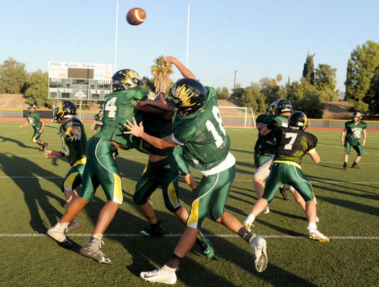 Quarterback Tanner Wolfe throws over teammates during Royal's practice Tuesday. The Highlanders host Simi Valley on Friday night with the Canyon League title on the line.