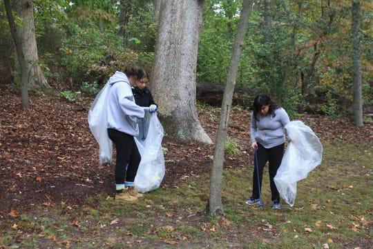 "(From left) Lexi Kelly, Maria Zarazua andAmy Morales participate in Bridgeton High School's ""Give Back"" cleanup of Bridgeton City Park."