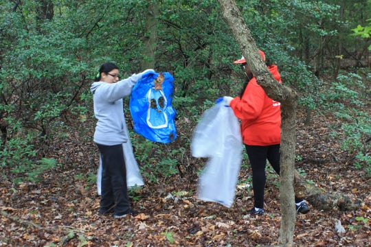 """Cindy Reyes (left) and Ashley Russell were among the participants in Bridgeton High School's """"Give Back"""" cleanup of Bridgeton City Park."""