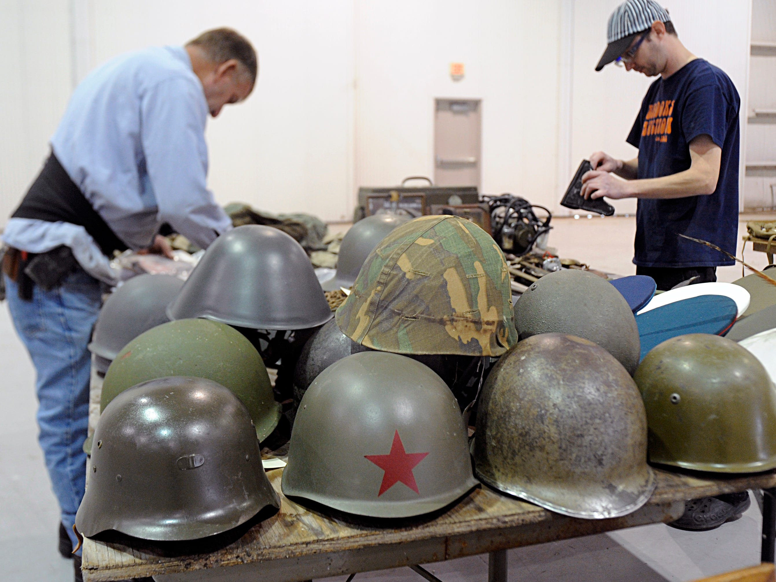 Brooks Auction staff set up items including practice bombs, artillery, swords and daggers for a military antiques auction at Millville Executive Airport.