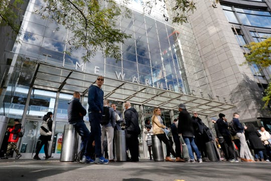 People gather outside the Time Warner Center in New York on Wednesday. A police bomb squad was sent to CNN's offices in New York City and the newsroom was evacuated because of a suspicious package. (Richard Drew/AP)