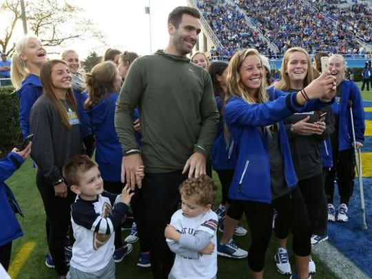 Joe Flacco poses for pictures with Delaware's field hockey players after he was introduced as a UD Athletics Hall of Fame inductee at halftime of the Towson game in 2016.