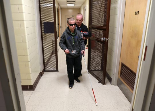 Job coach Jason Hannah helps Aaron Lynch navigate the hallways in the Zanesville Police Department, where Aaron types police reports. Once Aaron is used to the department, he will go to work by himself.