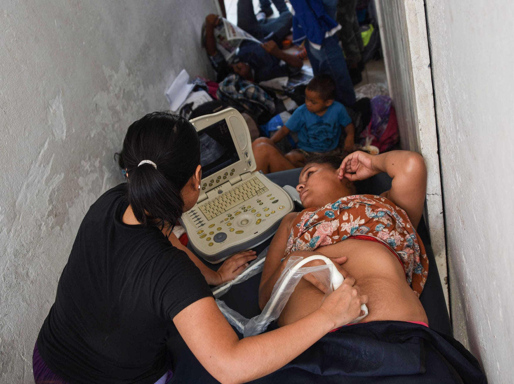 A Honduran migrant woman has an ultrasound done to check his pregnancy, on Tuesday, during a stop in their journey at the Central Park in Huixtla, Chiapas state, Mexico.