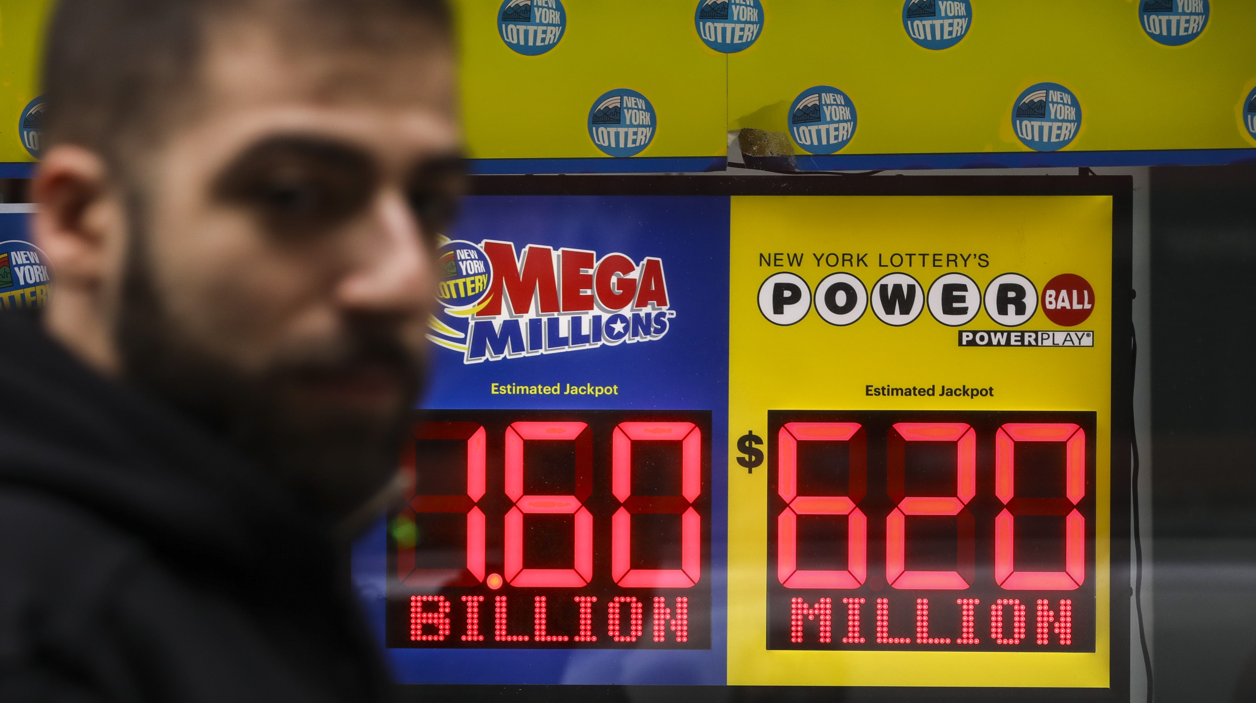 NEW YORK, NY - OCTOBER 23: A man walks past advertisements for the Mega Millions and Powerball lottery hanging on a window of the New York Lottery Customer Service Center, October 23, 2018 in New York City.