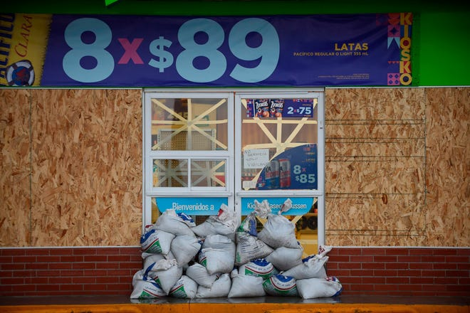 """View of a storefront with wood panels and sand bags for protection, as the Hurricane Willa arrives at the Mazatlan port in Sinaloa state, Mexico, on October 23, 2018. - Hurricane Willa was upgraded to a """"potentially catastrophic"""" Category 5 storm Monday off Mexico's Pacific coast, where it was expected to produce life-threatening wind and flooding, the US National Hurricane Center said. (Photo by ALFREDO ESTRELLA / AFP)ALFREDO ESTRELLA/AFP/Getty Images ORIG FILE ID: AFP_1A92H3"""