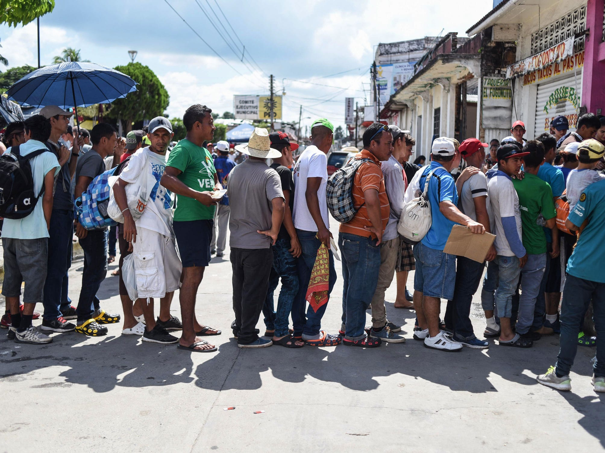 Migrants queue, Tuesday, to receive food during a stop in their journey, in Huixtla, Chiapas state, Mexico.