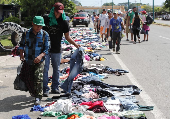 Migrants select clothing placed along the road by Mexican citizens during their journey to the United States, in Huixtla, Mexico. Hundreds of Mexicans distribute, altruistically from vehicles or on foot, food, water, medicine or clothing. 'The heart hurts when you see the children and there we feel the humanity of them, and how the Government does nothing', says Reina Lucia Ochoa, an inhabitant of the southeastern state of Chiapas.