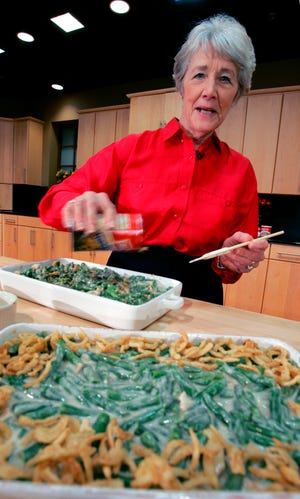 FILE - In this Nov. 15, 2005 file photo, a Green Bean Cassorole sits in the foreground as Dorcas Reilly prepares another at the Campbell Soup Co. corporate kitchen in Camden, N.J.  Reilly died on Monday, Oct. 15, 2018 and her family will celebrate her life on Saturday, Oct. 27 in the town where she lived, Haddonfield, N.J. Reilly was a Campbell Soup kitchen supervisor in 1955 when she combined green beans and cream of mushroom soup, topped with crunchy fried onions, for an Associated Press feature. It is the most popular recipe ever to come out of the corporate kitchen at Campbell Soup.  (AP Photo/Mel Evans, File)