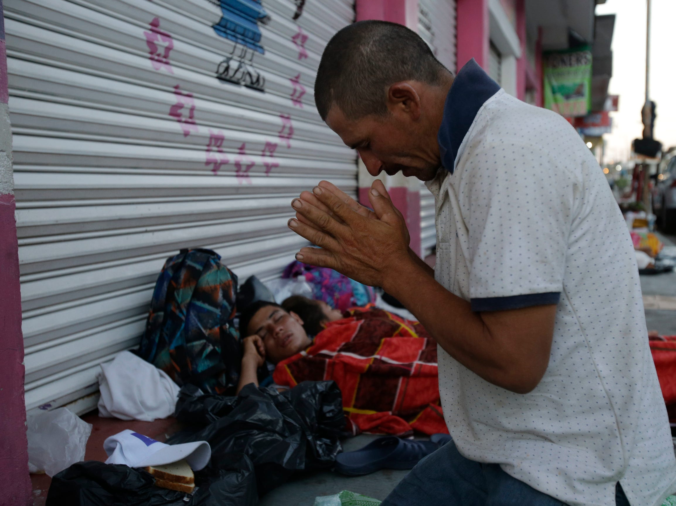 Marvin Sanabria, a Central American migrant traveling with a caravan to the U.S., kneels in prayer after waking up, in Huixtla, Mexico, Tuesday. The caravan, estimated to include more than 7,000 people, had advanced but still faced more than 1,000 miles, and likely much further, to the end of the journey.