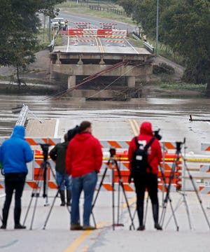 Reporters line up behind the barricades near where a bridge over the Llano River collapsed from floodwaters in Kingsland, Texas, on Oct. 17, 2018.