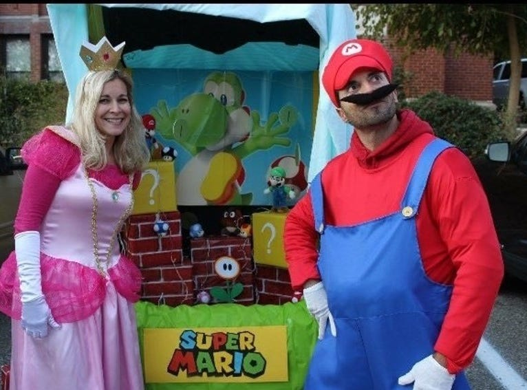 Super Mario themed trunk-or-treat photo of Michelle and Phil Cole.