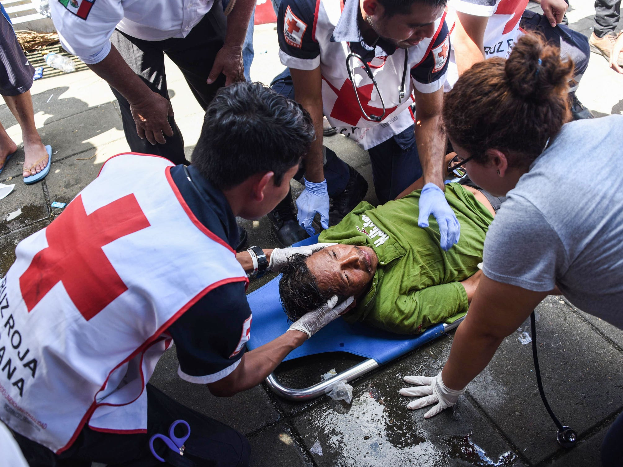 "A Honduran migrant is assisted after having a convulsion during a stop in Huixtla, Chiapas state, Mexico, on Tuesday. Thousands of mainly Honduran migrants heading to the United States -- a caravan President Donald Trump has called an ""assault on our country"" -- stopped to rest Tuesday after walking for two days into Mexican territory."