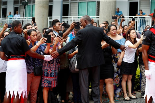 A crowd of people gather to take photos as Prince Harry and Meghan, Duchess of Sussex, visit the University of the South Pacific in Suva, Fiji.