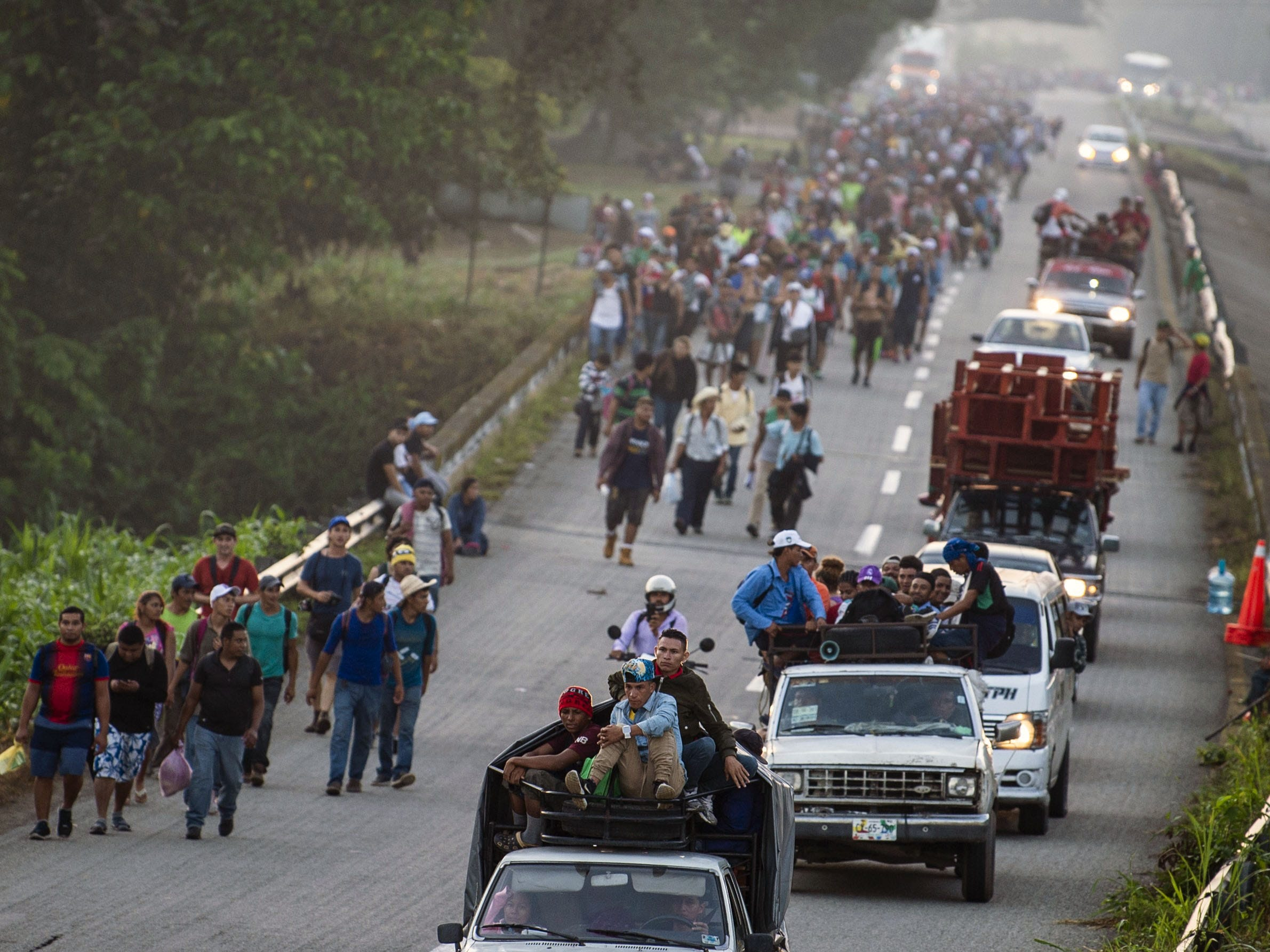 Central American migrants walking and aboard trucks head in a caravan to the U.S., in Huixtla, on their way to Mapastepec Chiapas state, Mexico, Oct. 24, 2018.
