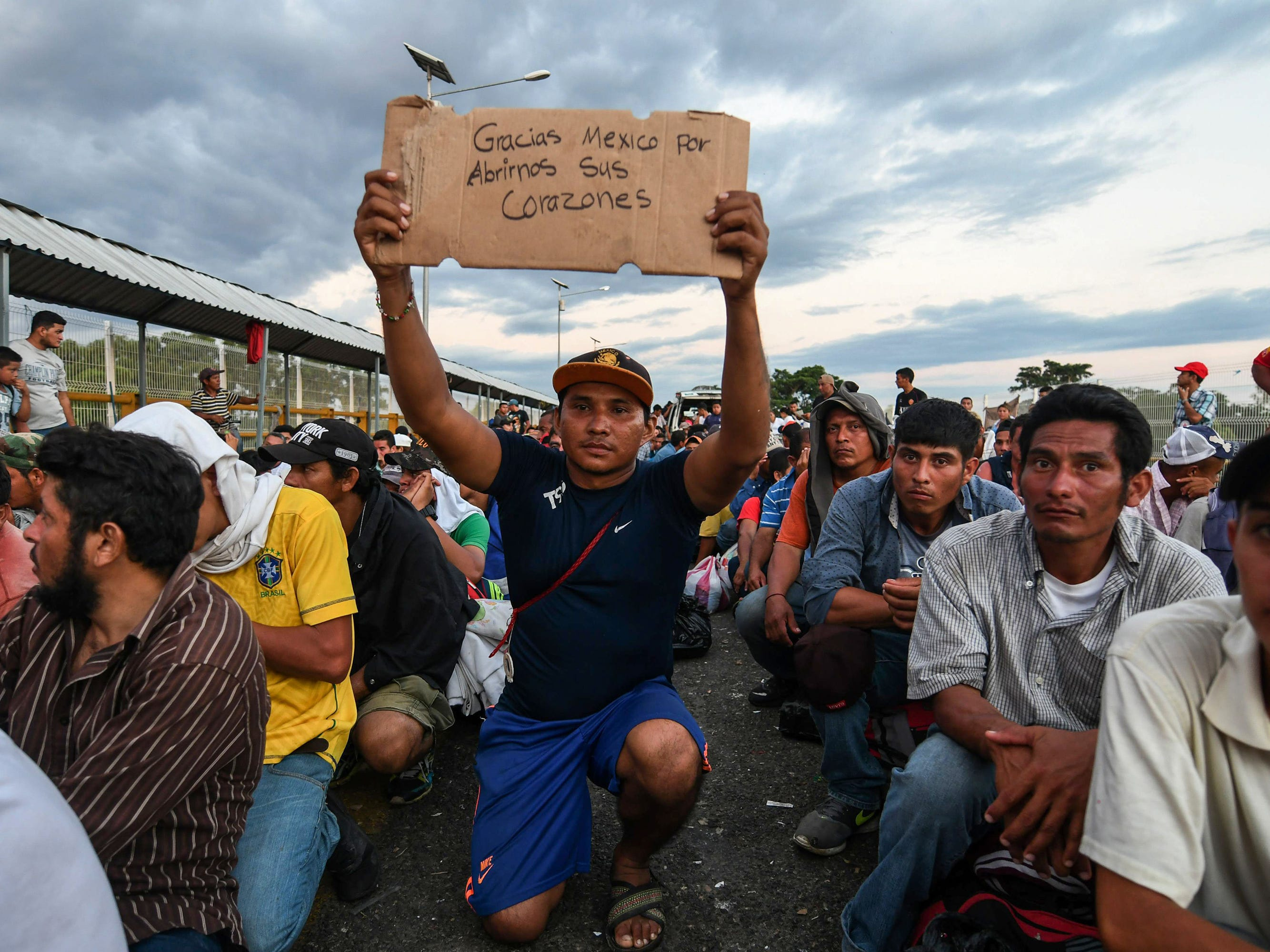 "A Central American migrant taking part in a caravan heading to the U.S., holds up a sign reading ""Thank you Mexico for opening your hearts to us,"" while he waits to cross the border from Ciudad Tecun Uman in Guatemala, to Ciudad Hidalgo, Mexico, Oct. 22, 2018."