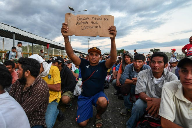 "A Central American migrant taking part in a caravan heading to the U.S., holds up a sign reading ""Thank you Mexico for opening your hearts to us,"" while he waits to cross the border from Ciudad Tecun Uman in Guatemala, to Ciudad Hidalgo, Mexico, on Monday, Oct. 22, 2018."