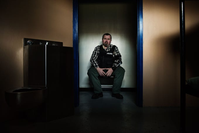 Daniels sits outside the jail cell at the police department in Seldovia.