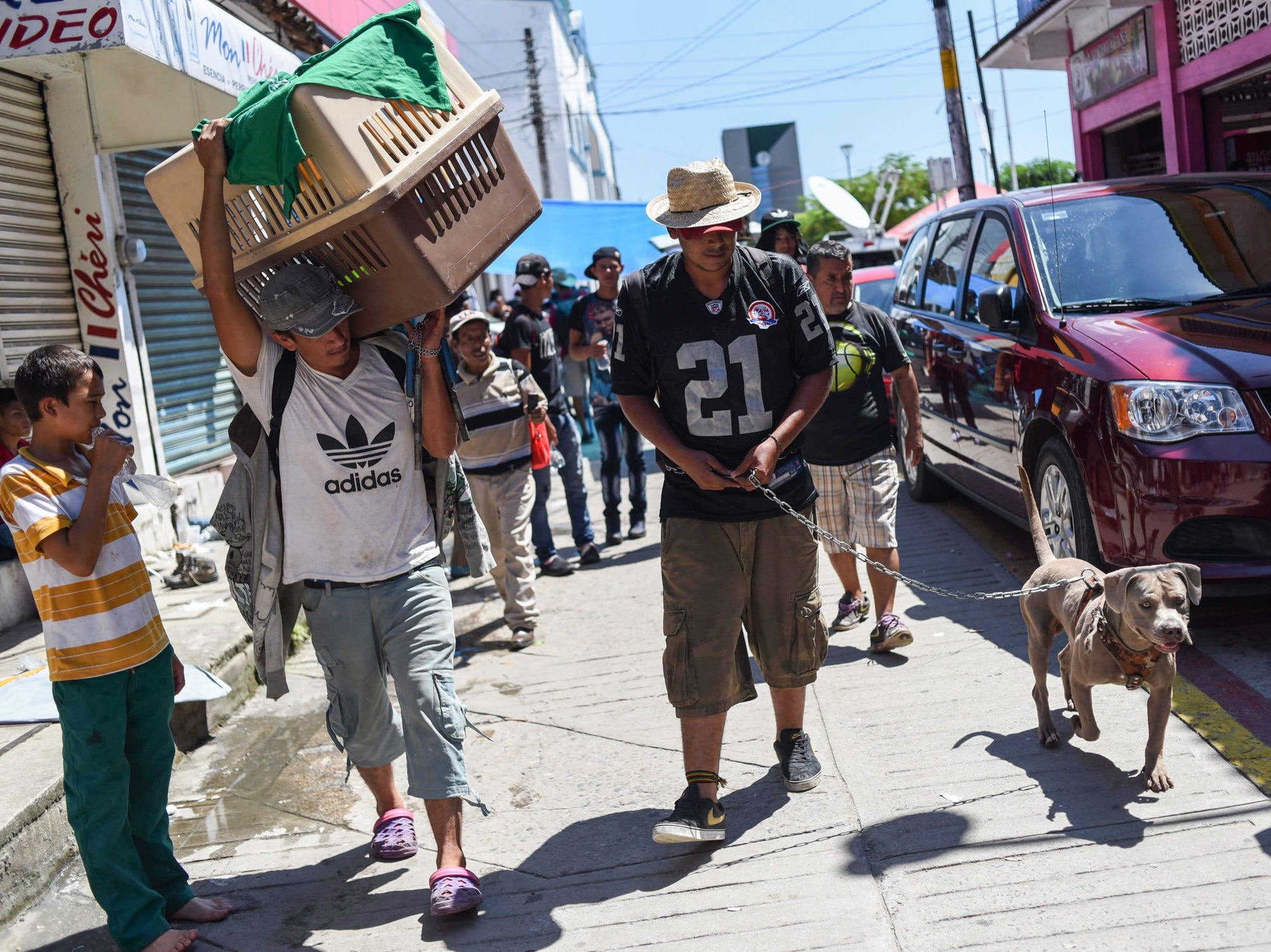 Honduran migrant, Luis Lopez, taking part in a caravan heading to the U.S., walks with his dog during a stop in their journey, in Huixtla, Chiapas state, Mexico.