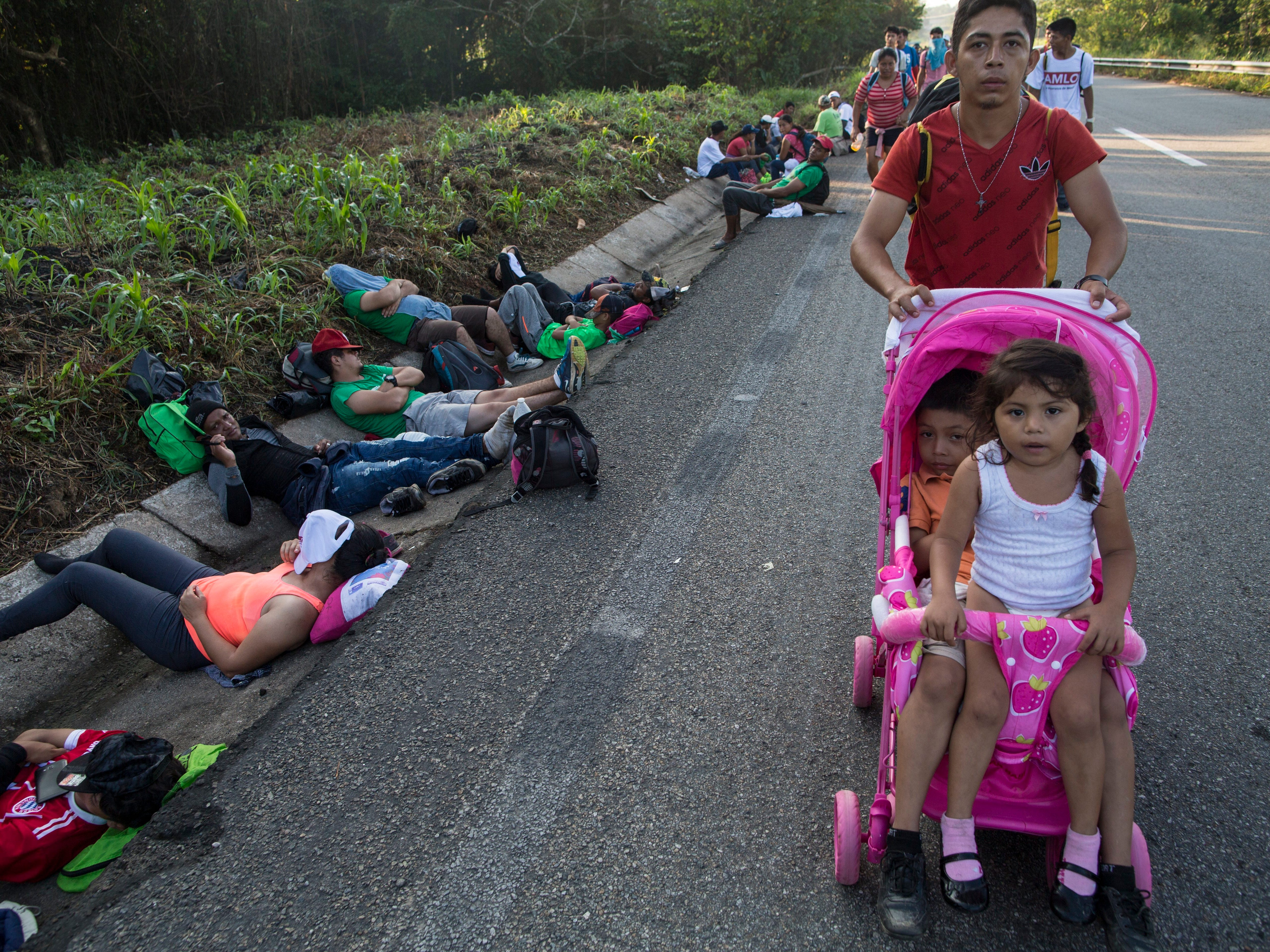 Central American migrant Cristian pushes a carriage occupied by his daughters; Karen, 5, left, and Beiyi, 4, as they make their way to Mapastepec, Mexico, Wednesday, Oct. 24, 2018, in a caravan headed to the U.S.