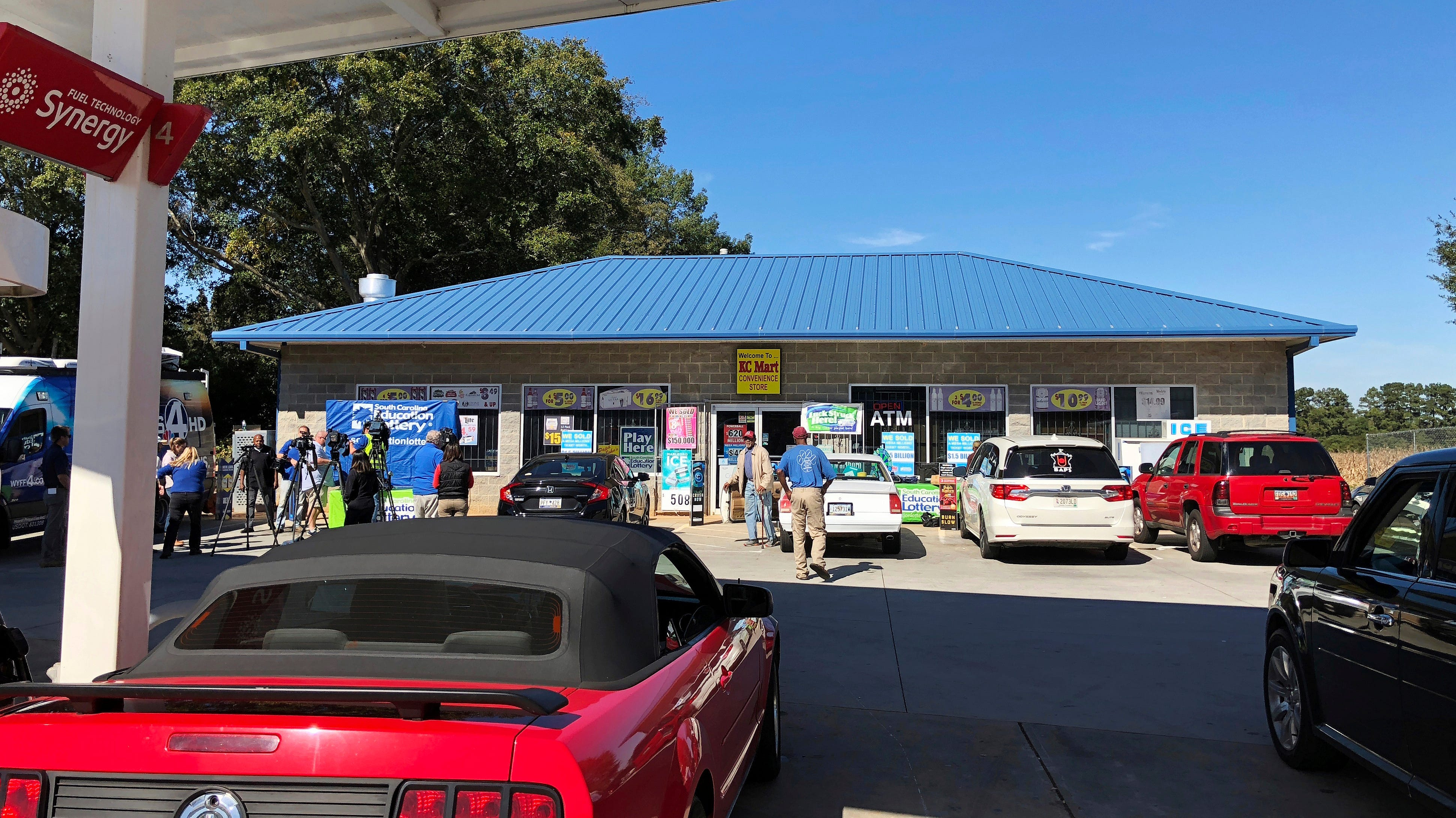 Media at left, record people entering the KC Mart in Simpsonville, S.C., on Wednesday, Oct. 24, 2018, after it was announced the winning Mega Millions lottery ticket was purchased at the store.