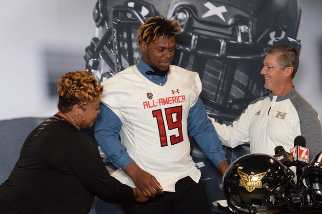 Zacch Pickens , a defensive end at TL Hanna High School in Anderson is honored by the American Family Insurance Under Armor All-American team with a jersey at the school athletic training center in Anderson on Thursday. On his left is Pickens' mother, Felicia Harris, with football coach Jeff Herron.