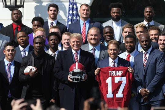 President Donald Trump poses with Alabama Crimson Tide head coach Nick Saban and members of the Crimson Tide a ceremony honoring the college football playoff champion in April.