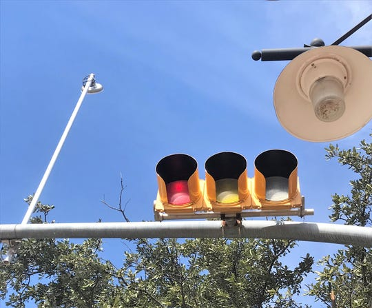 Long poles with radios have been attached to some traffic light crossbars so that lights can communicate with each other and send data to the city's traffic control center.