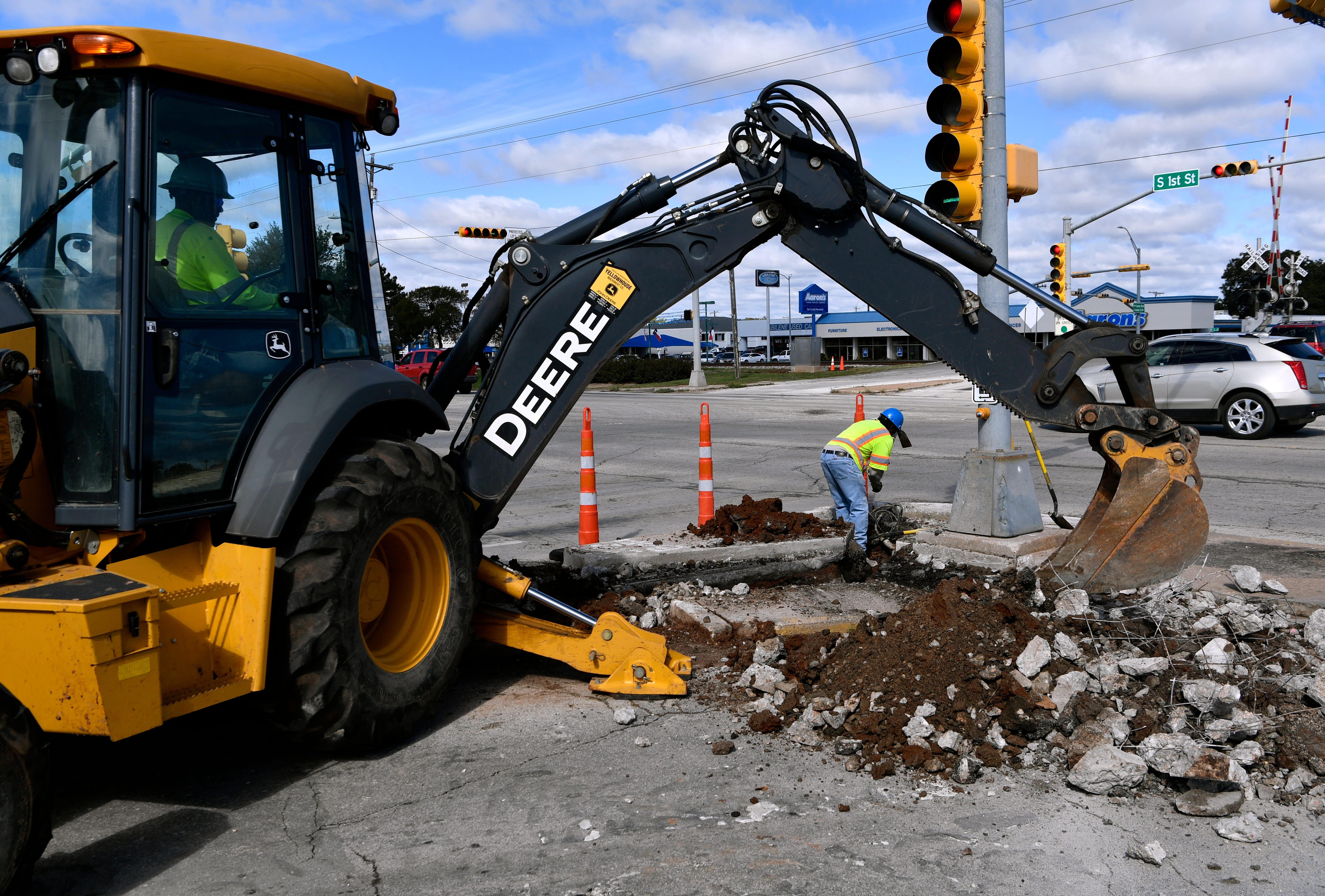 Workers dig beneath a traffic signal at South First Street and Sayles Boulevard Thursday. The men are installing traffic sensors there.