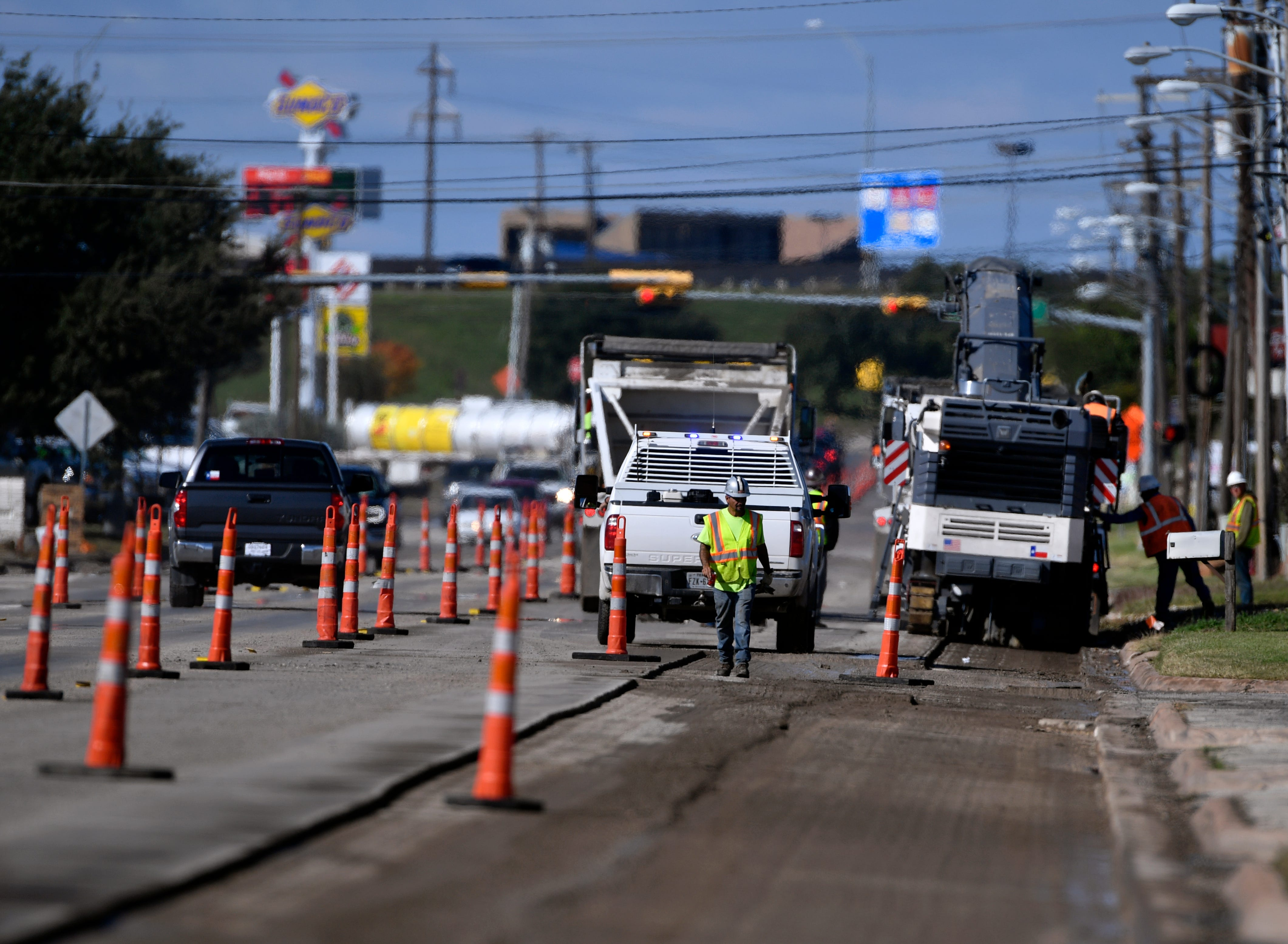 Construction workers strip the asphalt from Industrial Boulevard on Thursday.