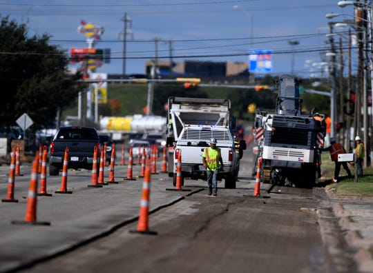 Construction workers strip the asphalt from Industrial Boulevard.