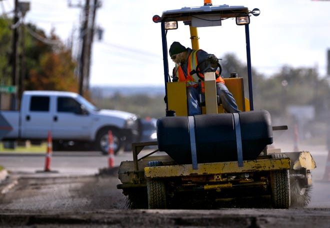 Grabiel Cerda of J.H. Strain & Sons works on Industrial Boulevard Thursday. Road work had resumed across the city now that skies and forecasts had finally cleared of wet weather.