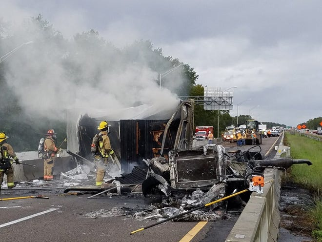 Firefighters doused a blaze aboard an overturned semi-truck Thursday on State Road 528 east of Orlando.