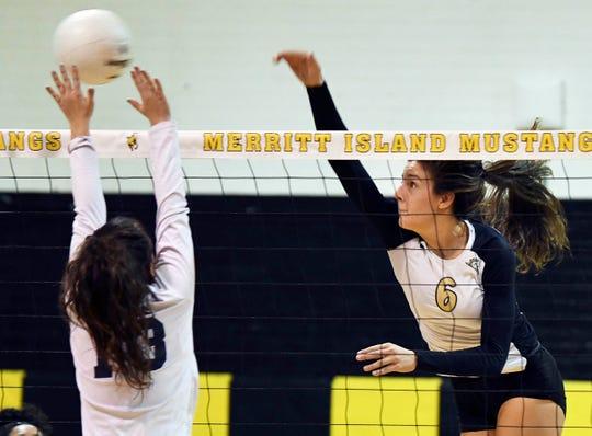 Lexy Denaburg of Merritt Island spikes past the block of Eustis defender Savannah Greene during the regional tournament.
