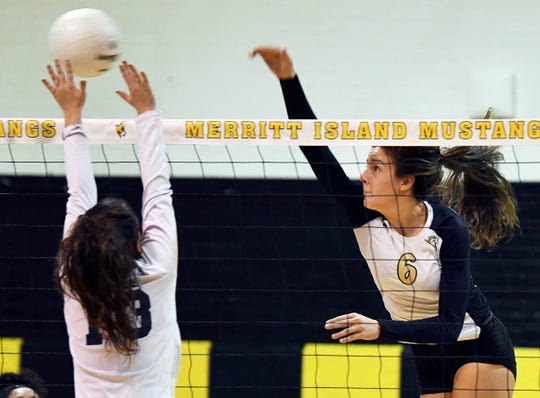 Lexy Denaburg of Merritt Island spikes past the block of Eustis defender Savannah Greene during the regional tournament.