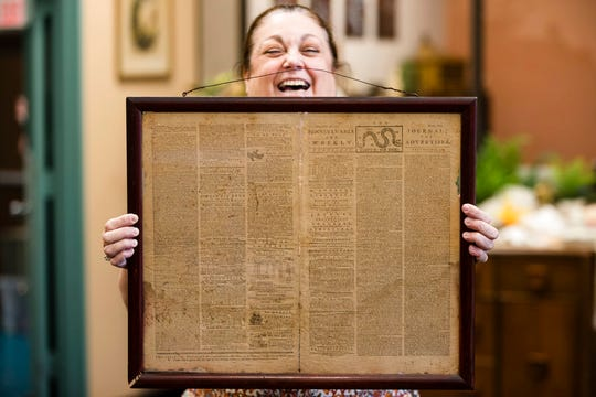 Heather Randall displays a Dec. 28, 1774 Pennsylvania Journal and the Weekly Advertiser at Goodwill Industries South Jersey in Bellmawr on Thursday.