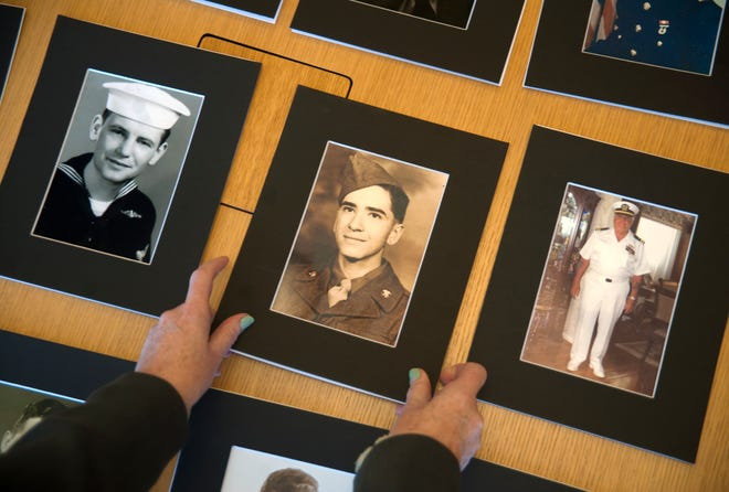 Cherry Hill Public Library Director Laverne Mann displays photographs of past and present Cherry residents who have served in the military and in war, that will be part of a veterans Wall of Honor exhibit opening at the library on November 18.