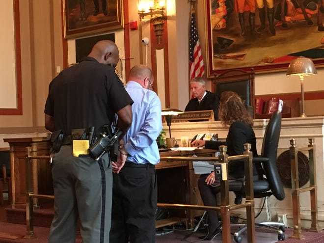 A sheriff's deputy handcuffs Trent Falcione, who was sentenced Thursday in Hamilton County Common Pleas Court to four years in prison for setting a fire in a file room at the General Electric Aviation facility in Evendale. Falcione pleaded guilty in August to a felony arson charge.