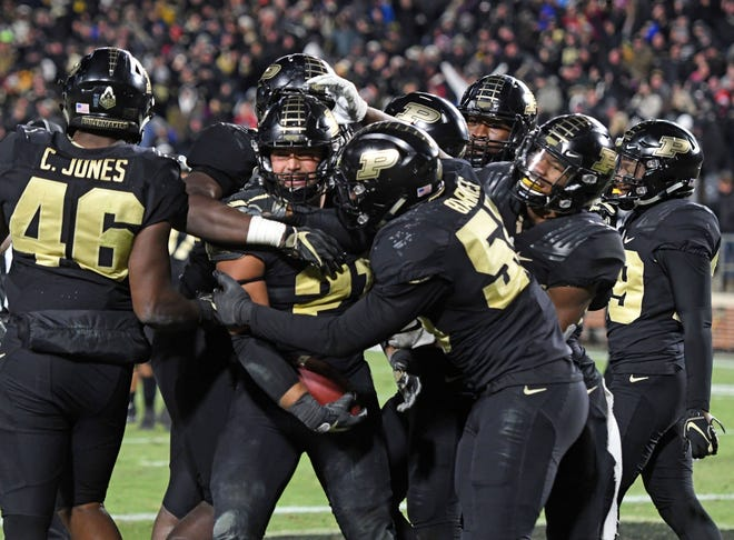 Purdue Boilermaker linebacker Derrick Barnes (55) celebrates with Markus Bailey (21) and teammates after Bailey scored a touchdown against the Ohio State Buckeyes in the fourth quarter  at Ross-Ade Stadium.