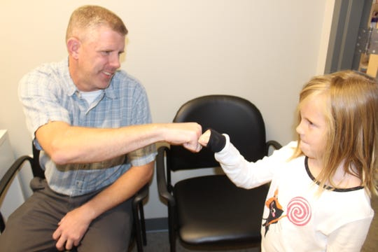 Keith Schaper of Clarksville fist bumps his daughter Elliott after they both got their flu shots at Sango Pharmacy on Wednesday.