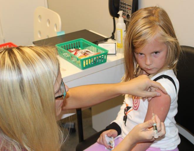 5-year old Elliott Schaper of Clarksville gets her flu shot Wednesday from pharmacist Clair Muiznieks at Sango Pharmacy.