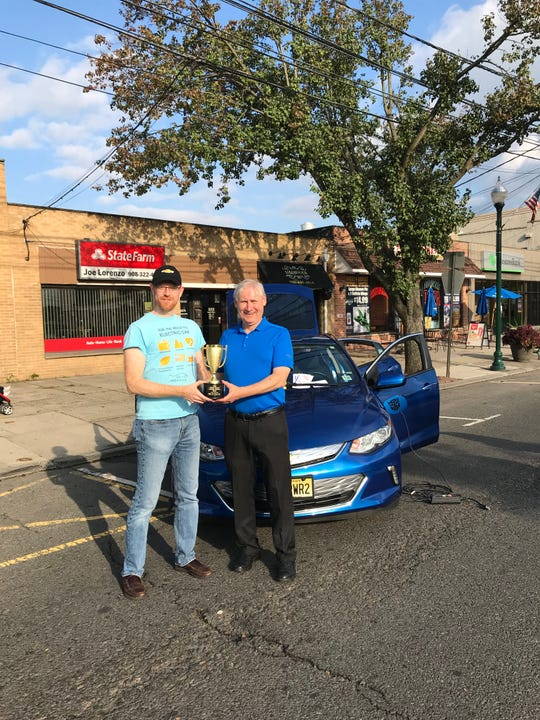 Mayor Al Smith (right) presenting the Best in Show trophy to Alex Brown for his 2016 Chevrolet Volt.