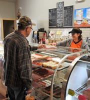 Ed Johnson receives a doughnut from Rachel Lahna at Ridgewood General Store. It features a deli, baked goods and ice cream among other foods.