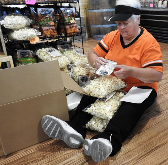 Ruth Opphile labels bags of popcorn for sale at Ridgewood General Store.