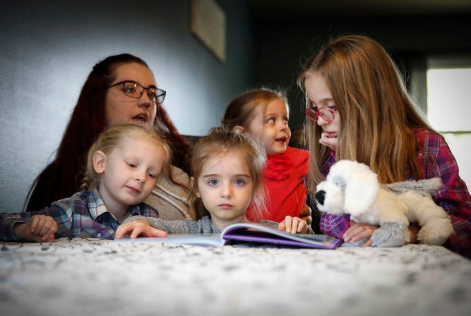 Adley Cooper, 3, reads a Peppa Pig book to her mother, Heather, and sisters Isabella, 5, left, Dahlia, 2 (in back), and Avalyn, 8, on Thursday, Oct. 25, 2018, in their Des Moines home. Adley has struggled with epilepsy the majority of her young life and Heather is hopeful legislation will pass in Iowa that will allow the use of medical marijuana to help ease the seizures.