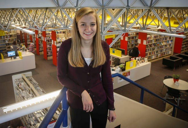 Ellie Hildebrandt poses for a photo inside the Des Moines Public Library on the south side, where she spends much of her time reading, studying and volunteering.