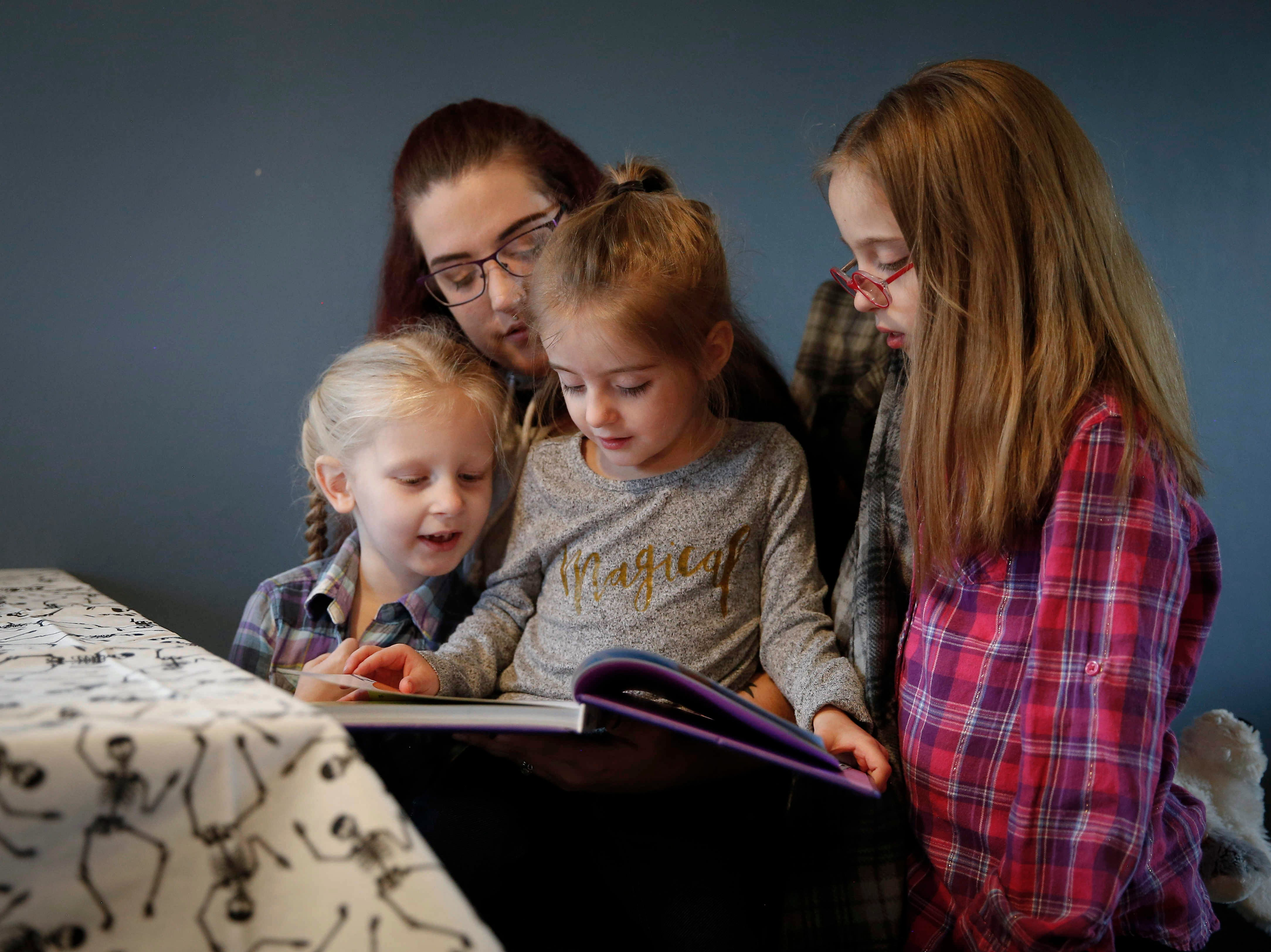 Adley Cooper, 3, reads a Peppa Pig book to her mother, Heather, and sisters Isabella, 5, left, and Avalyn, 8, on Thursday, Oct. 25, 2018, in their Des Moines home. Adley has struggled with epilepsy the majority of her young life and Heather is hopeful legislation will pass in Iowa that will allow the use of medical marijuana to help ease the seizures.